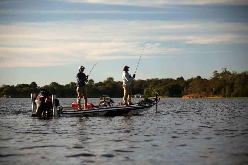 Two fishermen fishing in a bass boat on a lake.