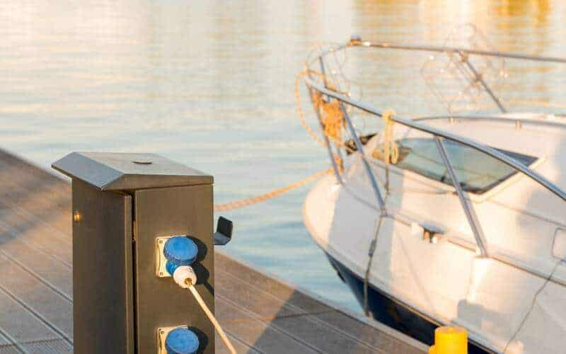 Boat attached to dock with deep cycle marine battery charging.