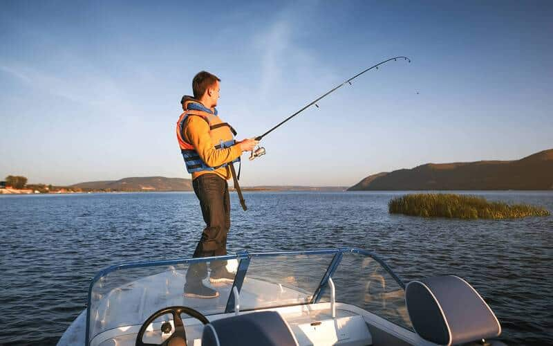 Man fishing off the back of a boat with hils in the background behind the lake.