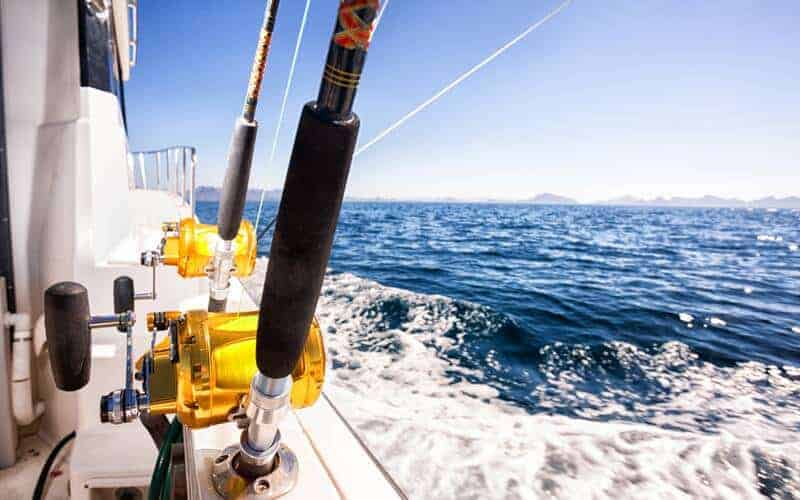 Fishing reels on a boat moving through the water with mountains in the distance.