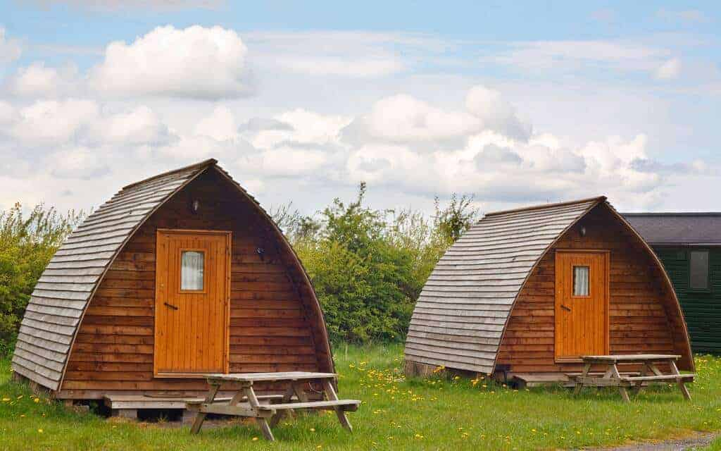 Two wooden tiny houses with picnic tables in front of them.