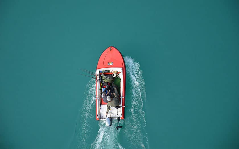 Two fishermen driving in a red bass boat on the lake.
