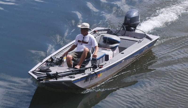 Fisherman driving a gray and blue bass boat on the lake.