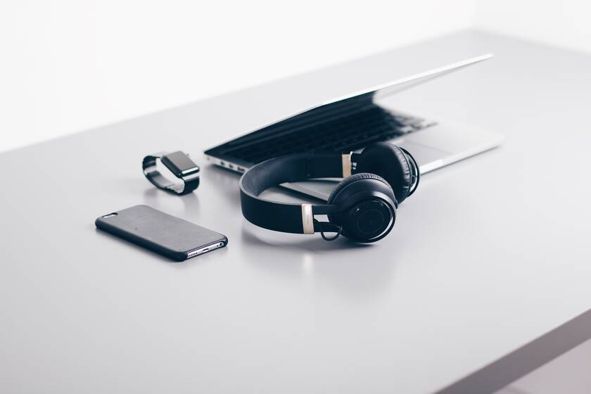 Cell phone, smartwatch, headphones and laptop on a table.