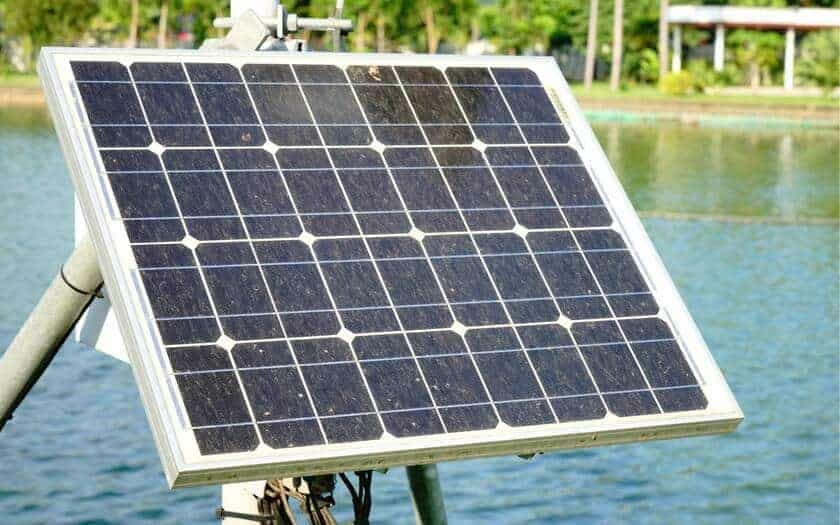 Portable solar panel with a lake in the background.