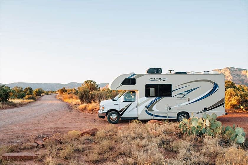 Rv parked in desert road with hills in the distance.