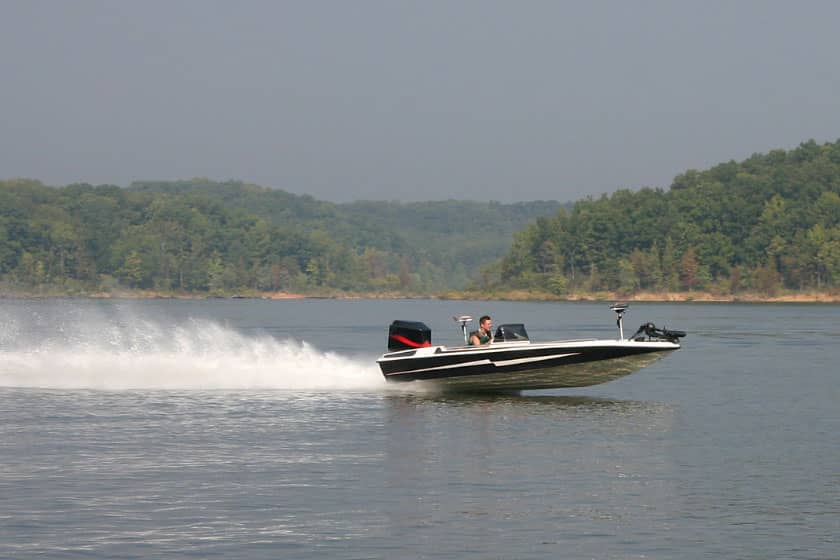 Bass boat with trolling motor speeding accross a lake with trees in the background.